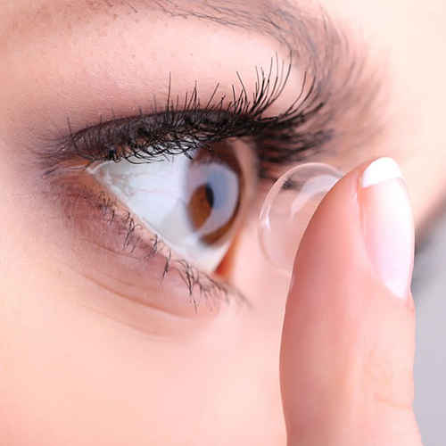 Contact lens fitting. Person inserting contact lens.